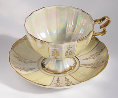 medalions in gold on an irridescent and pearly yellow cup and saucer with gilding