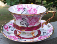 cup and saucer in cranberry and black with gilding trim on borders, rim, and handle